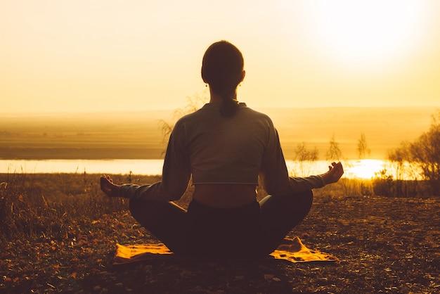 Vista traseira de uma garota meditando na natureza ao pôr do sol.