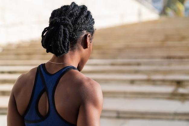 Vista traseira de uma garota negra afro vestida como uma corredora se preparando para começar a descer um lance de escadas na cidade