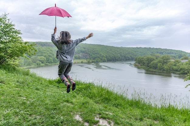 Vista traseira de uma garota sob um guarda-chuva, pulando perto de um lago em uma área montanhosa em tempo chuvoso.