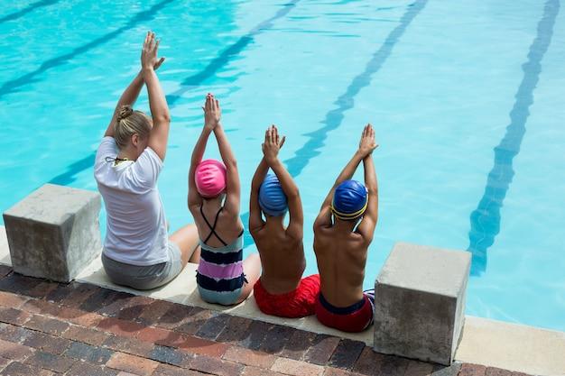 Vista traseira de uma instrutora de natação com alunos ao lado da piscina