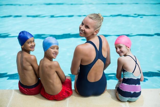 Vista traseira de uma instrutora de natação com alunos sentados à beira da piscina