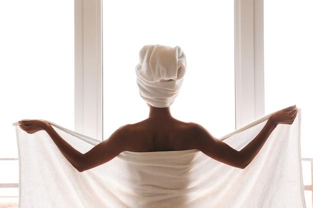 Vista traseira de uma jovem africana enrolada em uma toalha