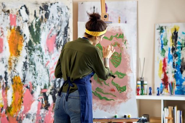 Vista traseira de uma jovem artista feminina pintando um avental em pé na sala de estar em casa
