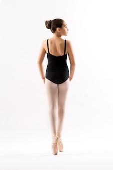 Vista traseira de uma jovem bailarina na ponta