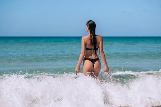 Vista traseira de uma jovem bonita fitness biquíni preto sexy com espólio desportivo em pé na água do mar. conceito de férias. férias de verão. turismo.