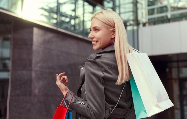 Vista traseira de uma jovem compradora loira sorridente em uma roupa da moda carregando sacolas de papel colorido em pé perto de um edifício urbano moderno, depois das compras