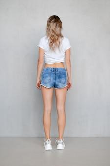 Vista traseira de uma jovem de shorts jeans e camiseta enrolada em pé com as mãos para baixo