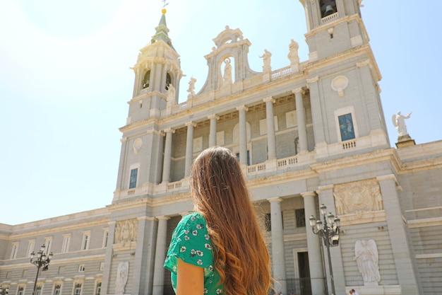 Vista traseira de uma jovem em madrid com a catedral de almudena, espanha