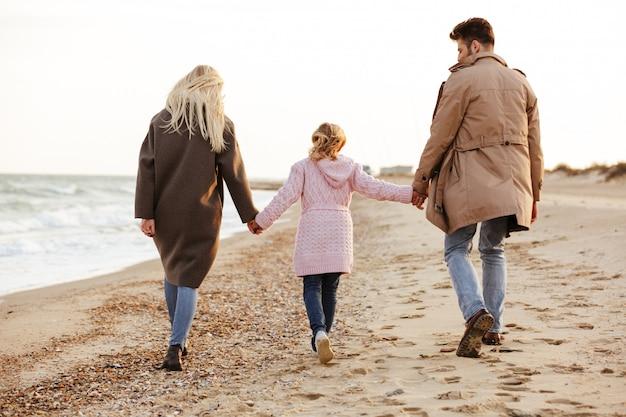 Vista traseira de uma jovem família com uma filha pequena