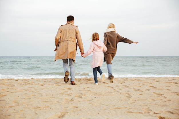 Vista traseira de uma jovem família com uma filha se divertindo na praia juntos e correndo