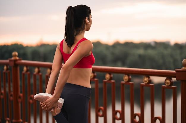 Vista traseira de uma jovem fitness com fones de ouvido fazendo exercícios de alongamento na ponte ao ar livre