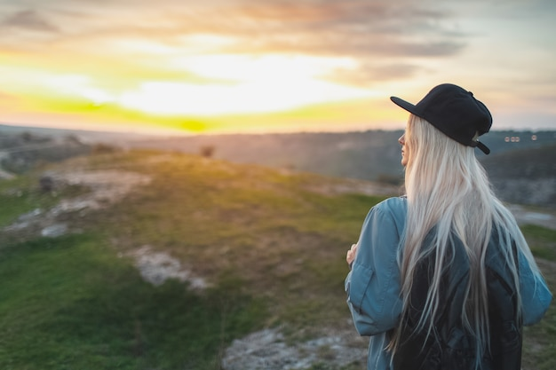 Vista traseira de uma jovem loira com boné preto e mochila, em pé no topo das colinas