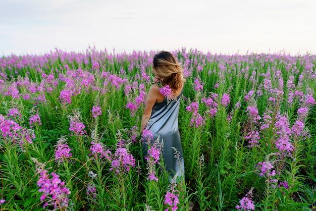 Vista traseira de uma jovem loira em pé com um vestido cinza e segurando um ramo de flores em um prado de erva-do-fogo