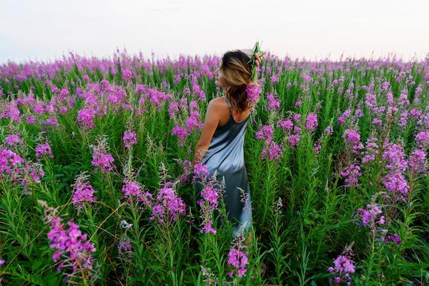 Vista traseira de uma jovem loira em pé com um vestido cinza e segurando um ramo de flores em um prado de erva-fogo