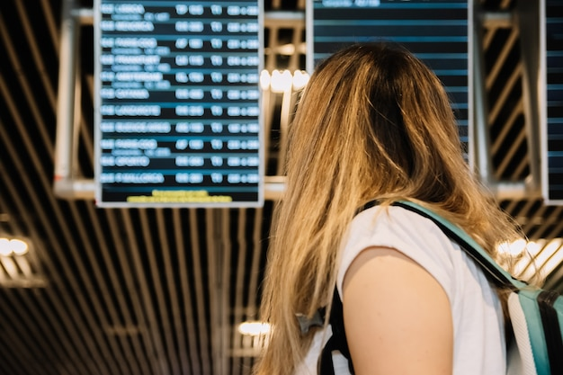 Vista traseira de uma jovem loira olhando para as telas de informações de voo do aeroporto.