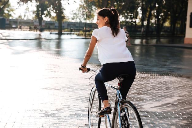 Vista traseira de uma jovem morena andando de bicicleta em uma rua da cidade