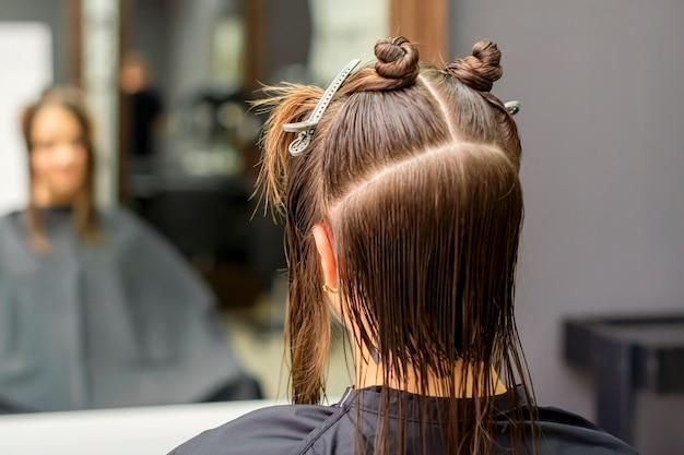 Vista traseira de uma jovem morena com cabelo dividido em seções em um salão de cabeleireiro