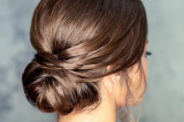 Vista traseira de uma jovem morena com um lindo penteado de coque médio cinza