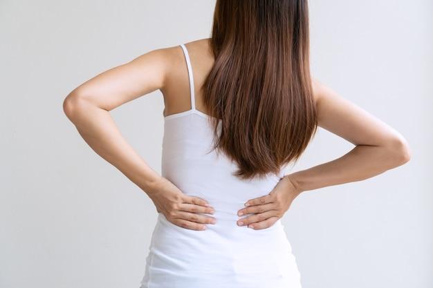 Vista traseira de uma jovem mulher asiática que sofre de dor nas costas, isolada no fundo branco. fechar-se