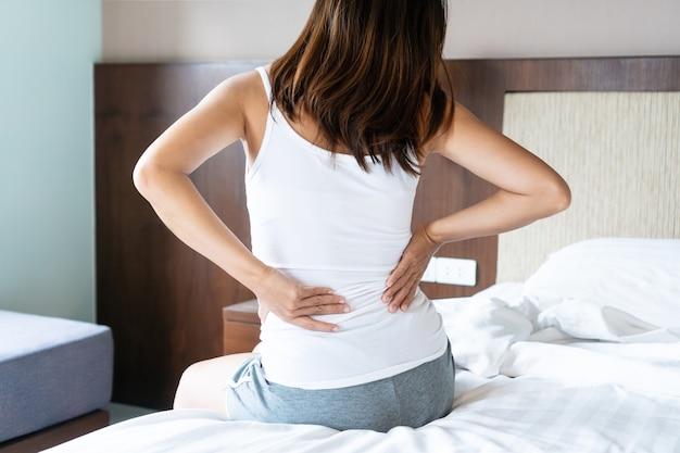 Vista traseira de uma jovem mulher asiática sofrendo de dor nas costas na cama em casa pela manhã