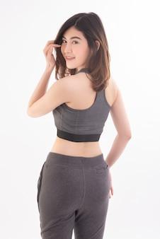 Vista traseira de uma jovem mulher asiática usar roupas esportivas fortes e músculos com saúde em branco