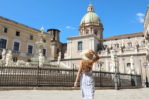 Vista traseira de uma jovem mulher bonita andando perto da monumental fonte pretoriana em palermo, itália.
