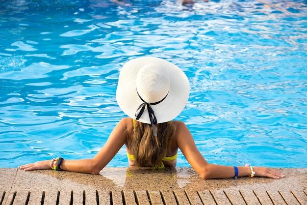 Vista traseira de uma jovem mulher com cabelo comprido, usando chapéu de palha amarelo relaxante na piscina quente de verão com água azul em um dia ensolarado.