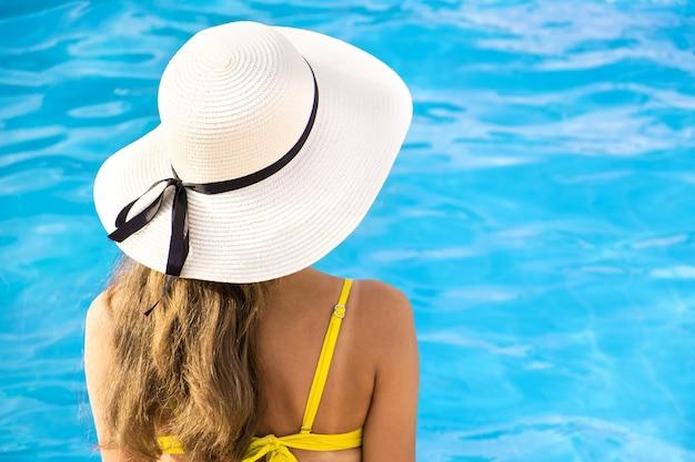 Vista traseira de uma jovem mulher com cabelo comprido, usando chapéu de palha relaxante no verão perto da piscina com água azul em um dia ensolarado.