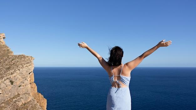 Vista traseira de uma jovem mulher desfrutando da liberdade com as mãos levantadas