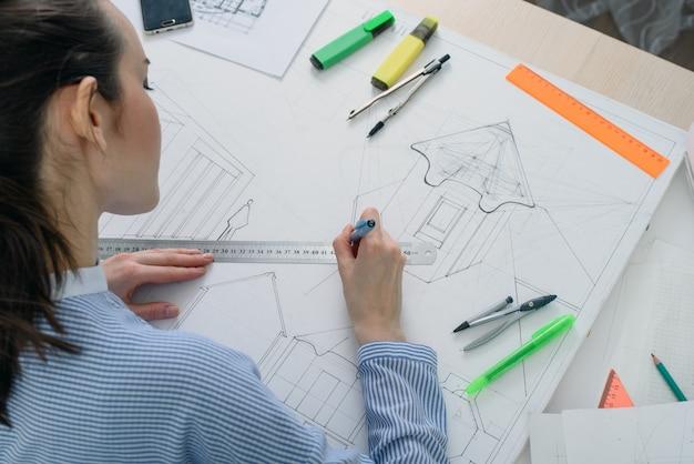 Vista traseira de uma jovem mulher prepara o trabalho arquitetônico na mesa com uma prancheta branca, régua e lápis