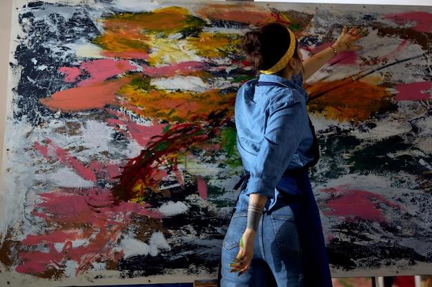 Vista traseira de uma jovem pintora de avental, olhando focada ao criar um grande e moderno