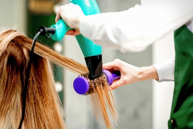 Vista traseira de uma jovem recebendo secando o cabelo com um secador de cabelo e uma escova de cabelo em um salão de cabeleireiro
