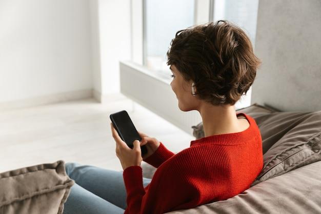 Vista traseira de uma jovem relaxando em casa, ouvindo música com fones de ouvido sem fio