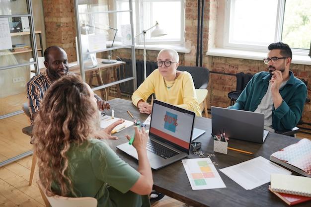 Vista traseira de uma jovem sentada à mesa com o computador e contando a seus colegas sobre o trabalho online durante uma reunião no escritório