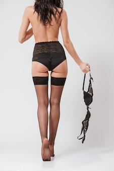 Vista traseira de uma jovem sexy andando de meias e segurando o sutiã isolado