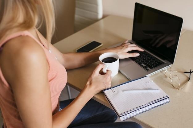 Vista traseira de uma jovem trabalhando em um laptop em casa