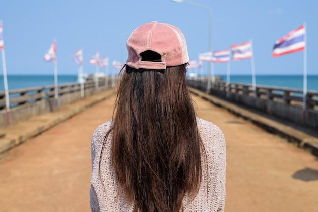 Vista traseira de uma jovem turista asiática no cais