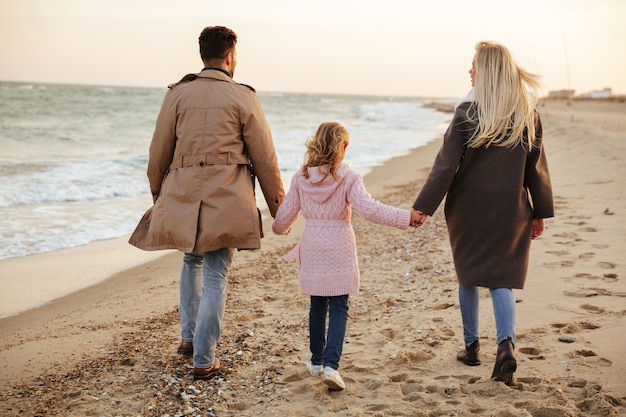 Vista traseira de uma linda família com uma filha pequena