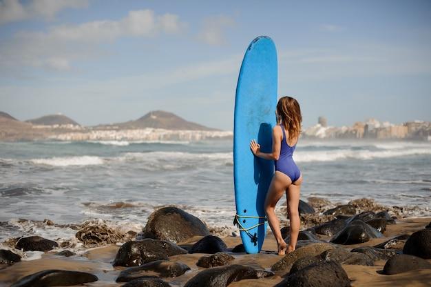 Vista traseira de uma linda garota de maiô azul em pé com a prancha de surf sobre o oceano atlântico