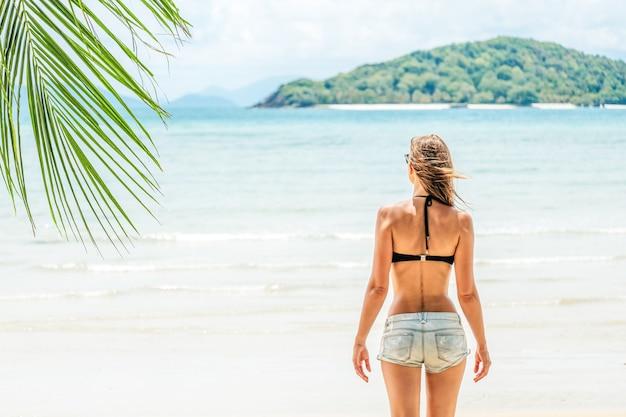Vista traseira de uma linda jovem morena, olhando para o oceano