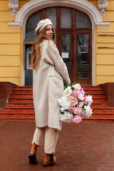 Vista traseira de uma linda mulher segurando um buquê de flores ao ar livre