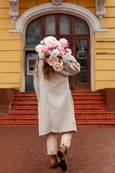 Vista traseira de uma linda mulher segurando um buquê de flores do lado de fora