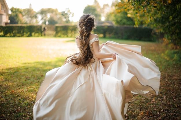 Vista traseira de uma linda noiva girando em um vestido de noiva dançando no campo verde em um dia ensolarado