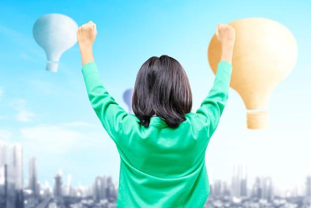 Vista traseira de uma menina asiática olhando para um balão de ar colorido voando com o plano de fundo da cidade