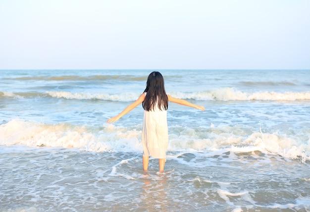 Vista traseira de uma menina asiática relaxando na praia