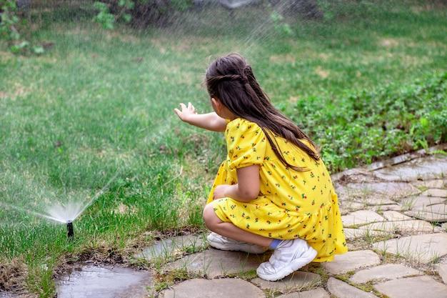 Vista traseira de uma menina brincando com gotas de água de um irrigador de gramado.