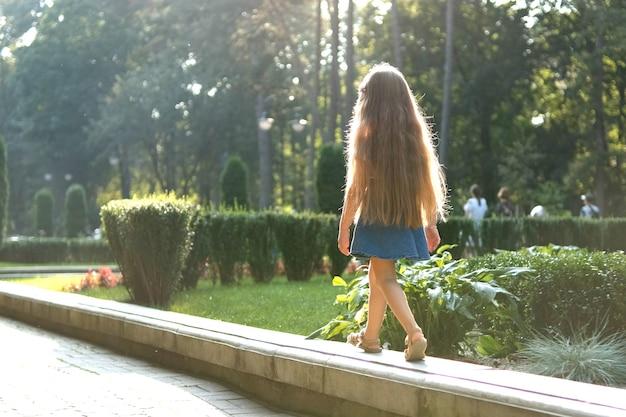 Vista traseira de uma menina criança bonita com cabelo comprido, caminhando ao ar livre no parque verde de verão em um dia ensolarado.