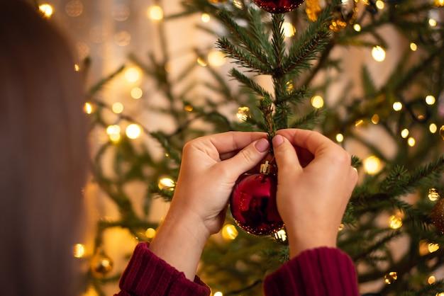 Vista traseira de uma menina morena com suéter cor de vinho, pendurando uma bola vermelha na árvore de natal