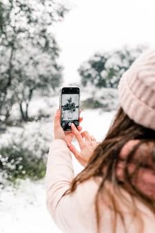 Vista traseira de uma mulher anônima em agasalhos quentes em pé na floresta e tirando fotos de uma paisagem de neve cênica enquanto usa o smartphone