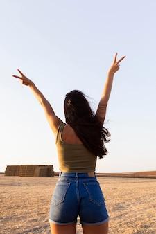 Vista traseira de uma mulher ao ar livre fazendo o sinal da paz com as duas mãos